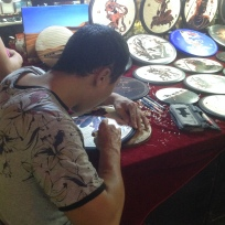 a man carving a wood picture to sell