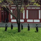 Sculptures of monks surrounding a tree